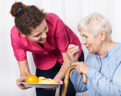 caregiver feeding elderly with fruits